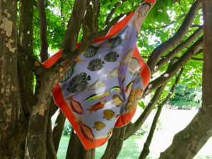 printed silk scarf with colorful fish hanging on tree