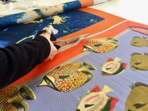 a person hand cutting printed silk panels on the table