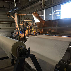 roll of silk fabric on the machine