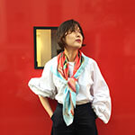 woman with red fish printed scarf against red wall