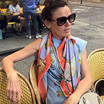 woman wearing fish printed silk scarf in a cafe