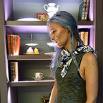 woman with blue mosaic silk scarf agains the shelf