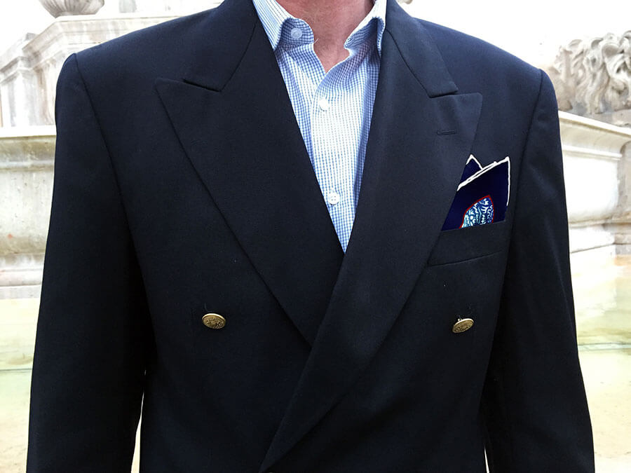 man in blue jacket with blue printed silk pocket square