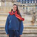 young parisien with red silk scarf tied around her sweater