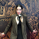 black beige silk scarf in bow under tailored jacket