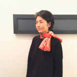red silk scarf on an artist in black