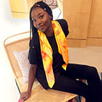 young woman with yellow silk scarf over black outfit