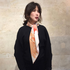 algae printed white silk scarf on a woman in black outfit