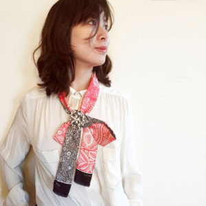 woman with pink and grey arabesque skinny silk scarf in a bow