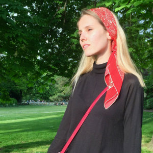 woman with red arabesque printed silk scarf worn on her head
