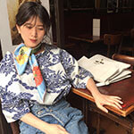 woman with printed shirt with cactus flower printed blue silk scarf in a French cafe