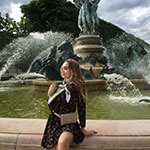young woman with cactus printed blue silk scarf in front of a fountain