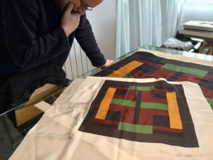 artist examining the silk scarf strike-offs