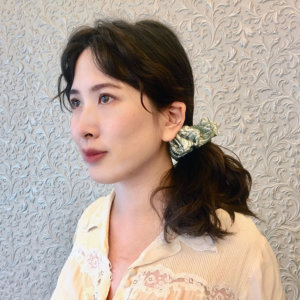 leaf printed sage silk hair scrunchy on woman in ponytail