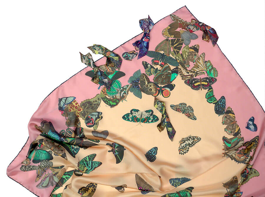detail of all over butterfly printed silk scarf and silk bow broach