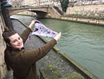 young woman holding artist collaboration silk scarf over the river Seine